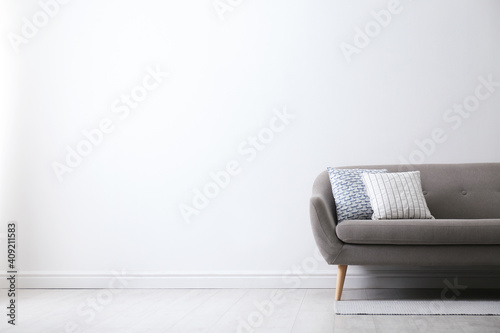 Obraz na plátně Grey sofa with pillows near white wall in stylish living room interior
