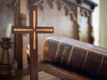 Large Holy Christian Bible Closed In Old Historic Church Of England Place Worship Wooden Cross In Focus Sermon Prayer From The Alter Rustic Used Old Book Leather Bound Light Reading Gods Word