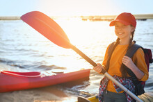 Happy Girl With Paddle Near Kayak On River Shore. Summer Camp Activity