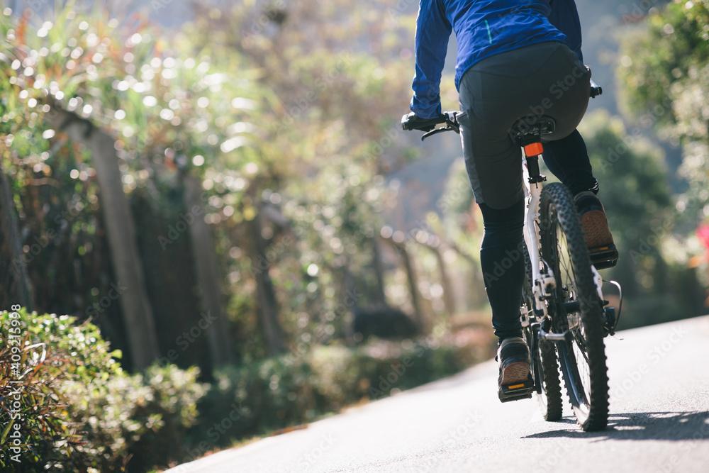 Fototapeta Woman riding a bike on tropical park trail in spring