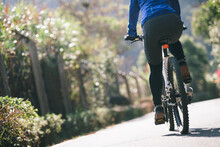 Woman Riding A Bike On Tropical Park Trail In Spring
