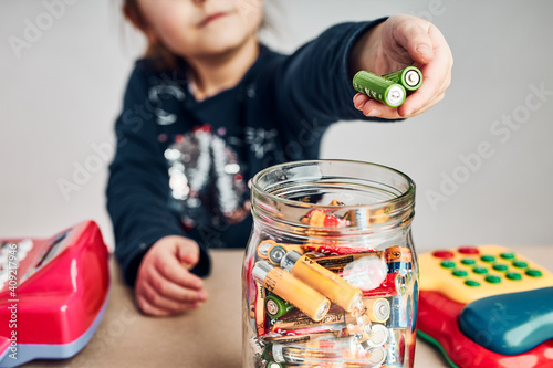 Obraz Little girl putting used batteries into jar for recycling. Child separating waste. Batteries only container - fototapety do salonu