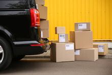 Black Delivery Van And Many Different Parcels Near Yellow Building Outdoors. Courier Service