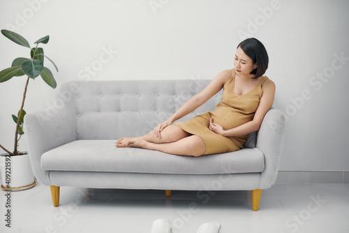 Fotografie, Obraz Pregnant woman massaging a swollen foot