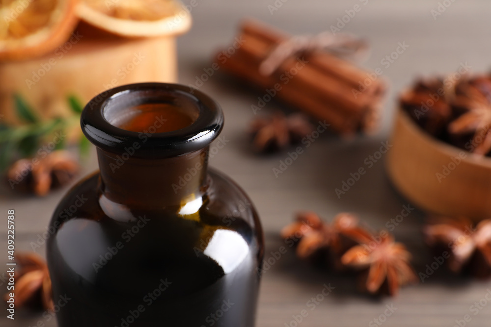 Fototapeta Anise essential oil in bottle on table, closeup. Space for text