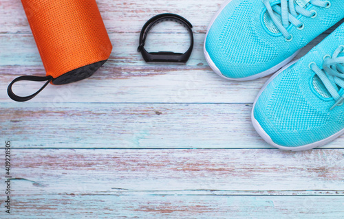Canvas Print watch, music and blue sports shoes on a rustic background, top view