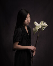 Classic Painterly Studio Portrait Of A Girl In Black Dress With A Branch Of White Lilac Spring Flowers
