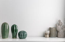 Decorative Artificial Ceramic Cactus, Succulent And Cactuses On White Wall Background. Candlesticks And  Candles.