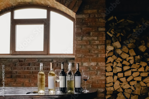 Bottles with white and red wine on rustic wooden table © Diana Vyshniakova