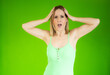 Leinwandbild Motiv Young blonde woman feeling horrified and shocked over green background.