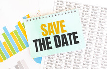 Green Notepad On Financial Documentation. Text Save The Date. Business Concept