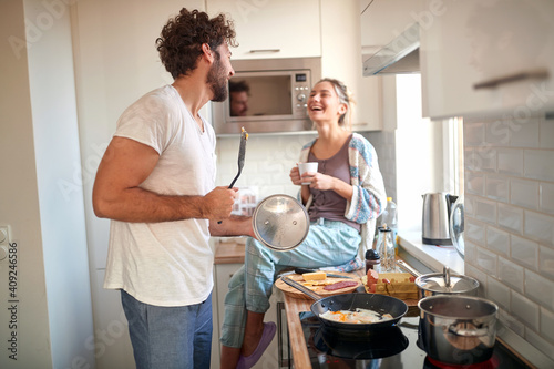 Fototapeta A young couple in love having fun while preparing a breakfast together