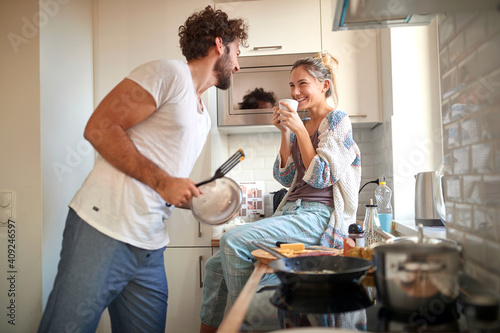 Obraz A young couple in love having good time while preparing a breakfast together. Cooking, together, kitchen, relationship - fototapety do salonu