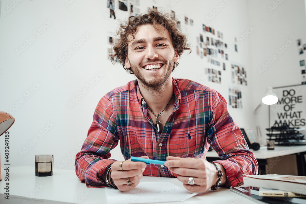 Fototapeta Happy man in shirt with a pencil poses in comfortable office sitting at table and looking at camera.