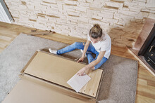 Above View Of Caucasian Girl Opening A Brown Paperboard Box With