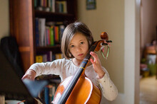 A Serious Little Girl Practices Cello In Beautiful Light At Home