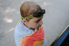 Boy Wrapped In Towel With Goggles On His Head And Wet Hair