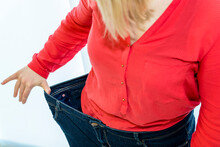 A Young Woman Shows Successher Weight Loss With Her Pants On