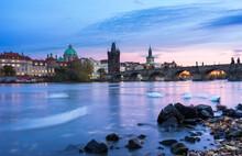 Swans Swimming In Vltava River Near Charles Bridge Against Sky At Sunset, Prague, Bohemia, Czech Republic