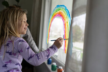 Side View Of Smiling Girl Painting Rainbow On Window