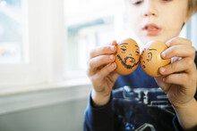 Toddler Boy Pretend Playing With Easter Eggs With Silly Cartoon Faces