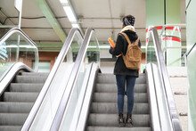 University Female African Student Wearing Protective Face Mask Taking Escalator Upstairs At The Underground Station. New Normal In Public Transport.
