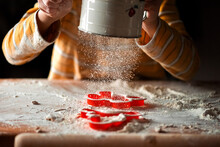 A Child Using A Flour Sifter Over A Cutting Board And Cookie Cutters