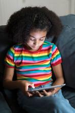 Ten Year-old Bi-racial Girl Looking At Ipad On Sofa