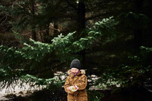 Happy Child Making Snowball Near Fir Tree In Forest