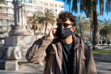 Man With Face Mask And Sunglasses Calling On The Phone On The Street