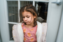 Girl In Christmas Pajamas Rests Against Door Outside