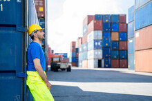 Portrait Of Container Worker Leaning On Cargo Container And Look