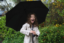 A Girl With Long Curly Hair Under An Umbrella Smiles Broadly.