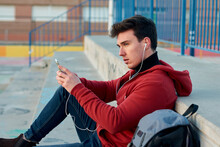 Student Man Holds His Mobile And Listen To Music In A Basketball Court
