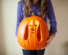 Close Up Of Tween Girl Holding Up Carved Pumpkin Of Dog Against Wall