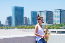 Woman With Ponytail Playing A Saxophone While Standing Outdoors