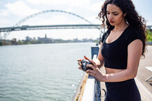 Woman Holding Camera Against Railing With River And Bridge