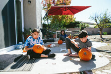 Three Kids Sit Outside And Carve Pumpkins