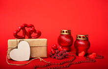 Gift In Craft Paper, Red Hearts With Red Candlesticks, Beads On A Red Background