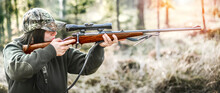 Hunting Gun In Female Hands Banner For Bussiness. Hunter With Rifle Is Aiming In Deep Forest. Shooter Sighting In To The Monocular.
