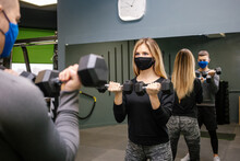 Woman With Protective Mask In Gym With Trainer