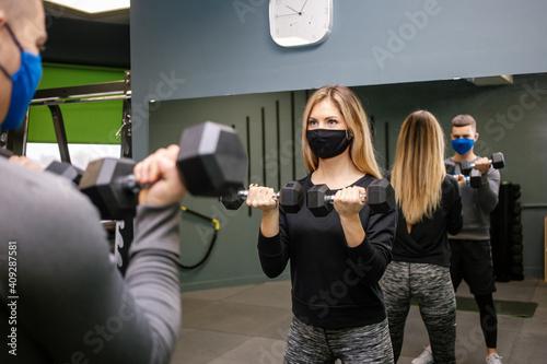 Billede på lærred woman with protective mask in gym with trainer