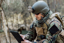 Bearded Soldier In Uniform Sit On Military Transport Crates, Analyze Data On A Tablet And Work Out Tactics At A Temporary Forest Base. In The Background, You Can See A Soldier Protecting The Base.