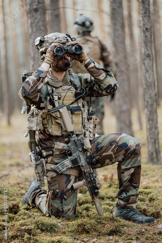 Portrait of a bearded middle-aged soldier in a Woodland military uniform and a helmet with headphones on his head, holding a rifle and looking around through the thick pine woods Fototapeta