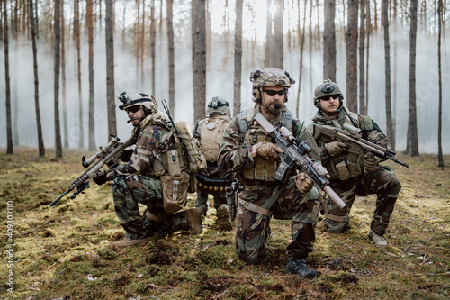 Four fully equipped, middle-aged soldiers in camouflage uniforms form a line, ready to fire, aiming with their rifles Fototapeta