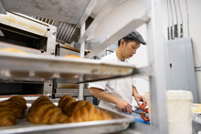 Male Baker Slicing Strawberries Behind Croissants In Bakery Kitchen