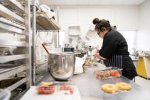 Female Baker Filling Donuts In Commercial Bakery Kitchen