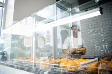 Male Baker Arranging French Pastries In Bakery Display Case