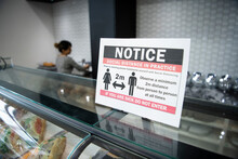 Close Up Social Distancing Reminder Sign On Display Case In Bakery