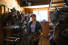 Smiling Female Rancher Carrying Saddle